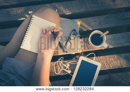 Young hipster woman writing journal on small notebook while sitting on wood litter in early morning time on weekend with vintage filter effect