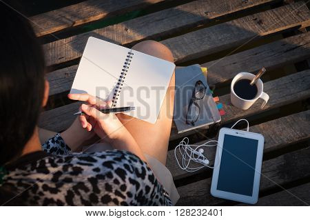 Young hipster woman writing journal on small notebook while sitting on wood bridge in early morning time on weekend with high contrast sun lighting