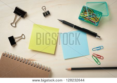Sticky paper including blue and green color with blank area for text or message stick on wood table with pen pencil paper clips and notebook in morning time