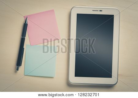 Small tablet pc with blank area on touchscreen and sticky paper with blank copy space on wood table with vintage filter effect