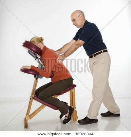 Caucasian middle-aged male massage therapist massaging back of Caucasian middle-aged woman sitting in massage chair.