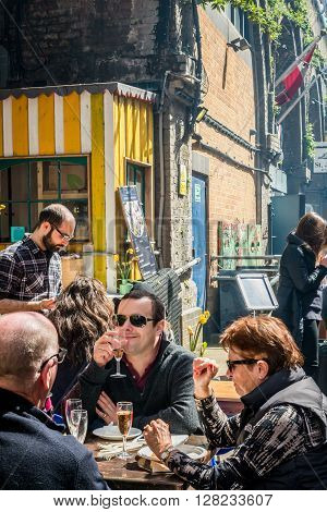 London United Kingdom - April 30 2016: Maltby Street Market in Bermondsey (located in railway arches SE1 Rope Walk). Great artisan street food stalls and bars. People enjoying drinks and sunshine