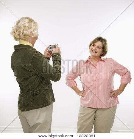 Caucasian senior woman taking photo with digital camera of middle aged woman.