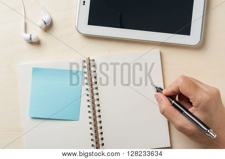 Young man right hand writing on notebook with sticky paper beside small tablet pc and in ear headset on wood table