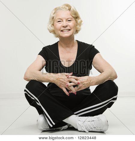 Caucasian senior woman sitting on floor with legs crossed.