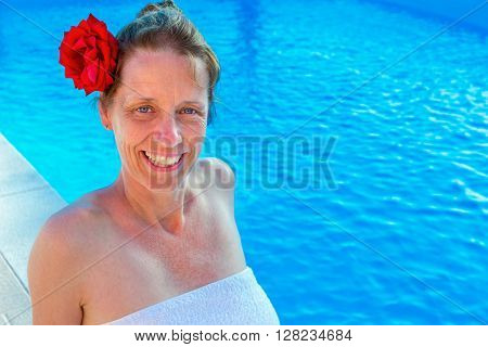 European middle aged woman with red rose in hair and towel at swimming bath