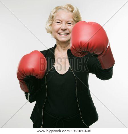 Mujer caucásica de senior con guantes de boxeo y lanzar el golpe en el espectador.