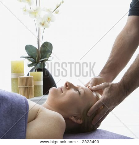 Caucasian middle-aged male massage therapist massaging temples of Caucasian middle-aged woman lying on massage table.