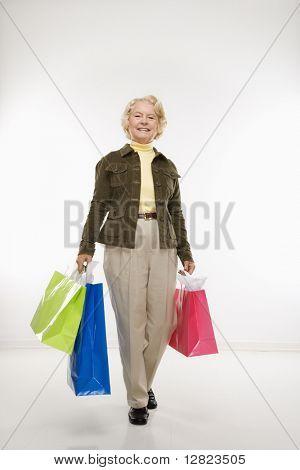 Caucasiana sênior mulher segurando sacos de presente, sorrindo no visualizador.