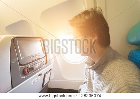 man looking out of the window in airplane