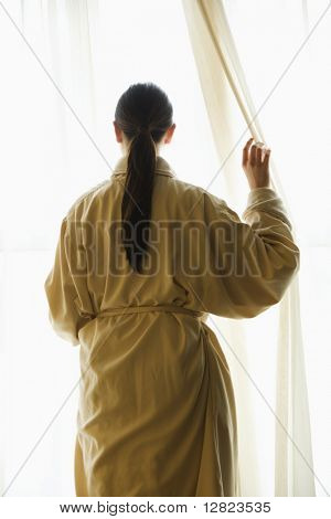 Taiwanese mid adult woman in bathrobe  looking out window.
