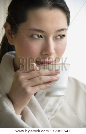 Taiwanese mid adult woman in bathrobe drinking coffee and looking to side.