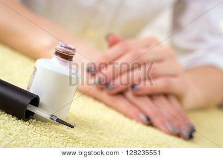 Woman hands with manicured nails closeup. Skin and nail care. Focus on brush
