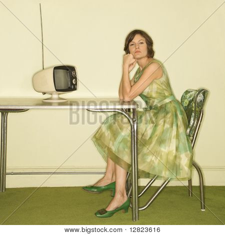 Pretty Caucasian mid-adult woman wearing green vintage dress sitting at 50's retro dinette in front of old televsion looking bored.