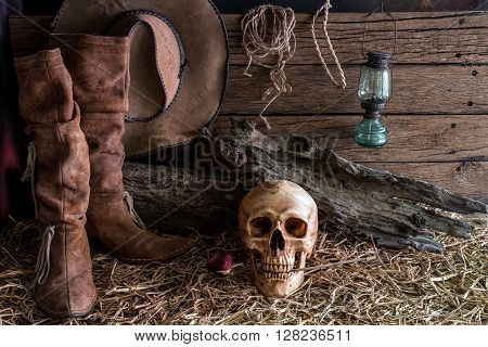 Still life human skull and rose on hay with traditional leather boots and american west rodeo brown felt cowboy hat background vintage and dark tone for horror halloween