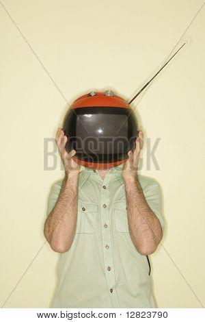 Hombre mid-adult caucásico que sostiene la televisión retro roja redonda en lugar de cabeza.