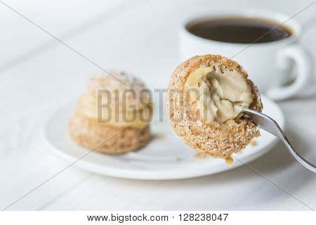 piece of pastries shu on a fork eating cake with coffee
