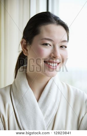 Taiwanese mid adult woman in bathrobe smiling at viewer.