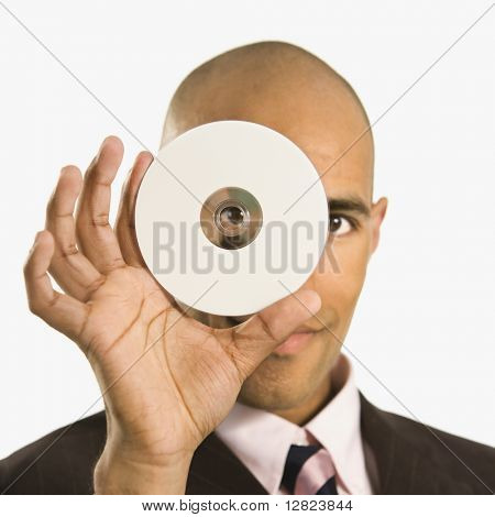 African American man holding compact disc over face and peeking through hole.