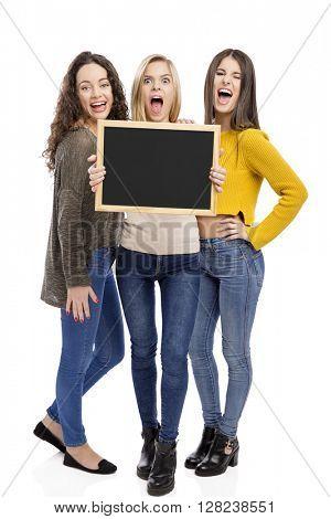 Studio portrait of three teenage girls holding a chalkboard