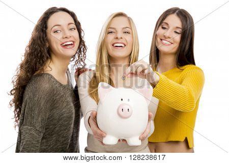 Studio portrait of three teenage girls holding a piggybank
