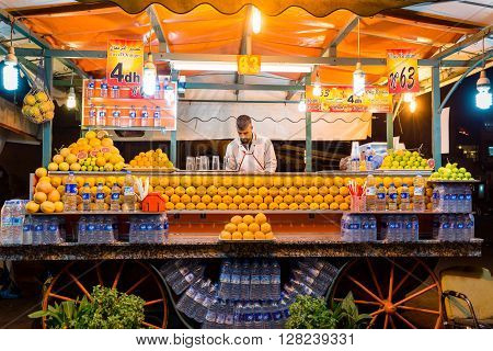 MARRAKECH MOROCCO - OCTOBER 20 2015: Unidentified man working on stand selling orange juice in Djemaa el Fna square central Marrakech Morocco.
