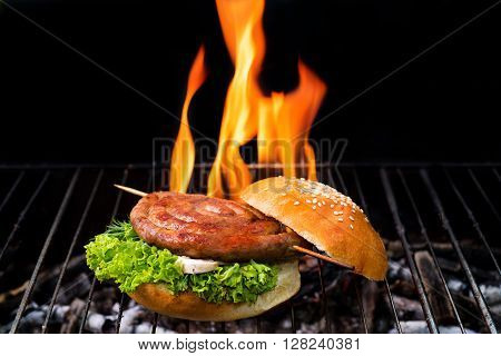 grill concept with flame. Burger and sausages on a grill pan.