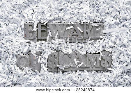 beware of scams phrase made from metallic letterpress type inside of shredded paper heap
