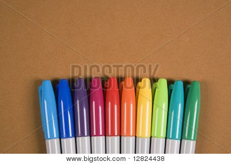 Group of colorful markers lined up in a row.