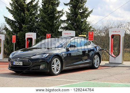 PAIMIO, FINLAND - APRIL 29, 2016: Black Tesla Model S electric car which operates as taxi cab is being charged at Tesla Supercharger Station of Paimio.