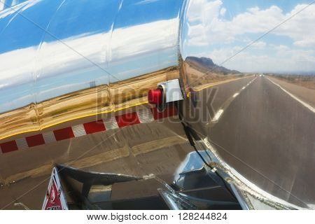 The road is reflecting in the gas tanker of a truck