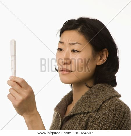 Asian mid adult woman holding up pregnancy test.