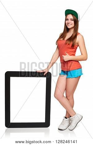 Portrait of happy teen funky girl in full length standing with empty frame - blank copy space, over white background