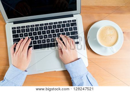 Top view of woman typing on notebook computer