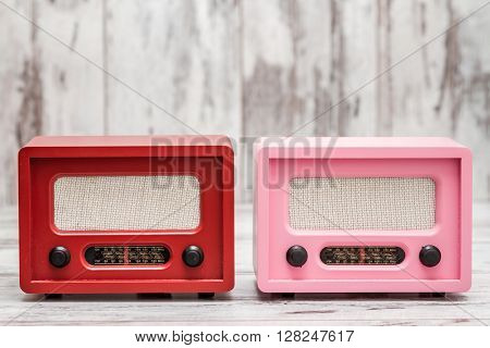 Pink and red radio with retro look on white wooden background