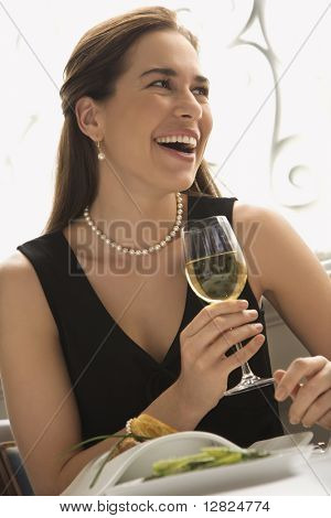 Mid adult Caucasian woman smiling and drinking white wine in restaurant.