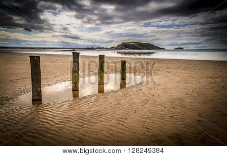 Th sky is reflected in pools around marker posts in the wet sand