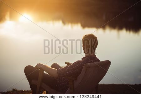 Man in the seat at bank of  lake also looks afar on sunset. Relaxing and freelance concept.