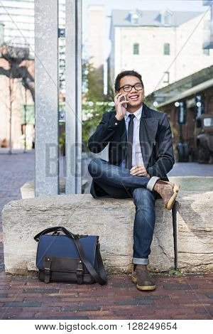 Happy young asian business man talking on mobile phone sitting outside on city street