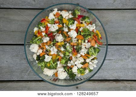Fresh vegetable salad with cauliflower, broccoli, carrots and peppers in glass bowl, overhead view