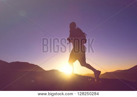 Man's silhouette running in a sunset with mountain range as a background.