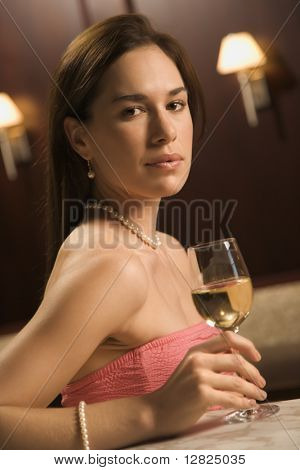 Mid adult Caucasian woman sitting at bar with glass of white wine looking at viewer.