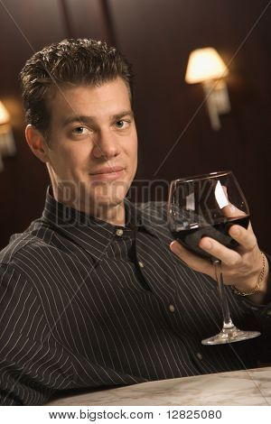 Mid adult Caucasian man holding glass of red wine and looking at viewer.