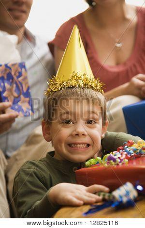 Niño caucásico en fiesta de cumpleaños, mirando al espectador, haciendo la expresión facial.