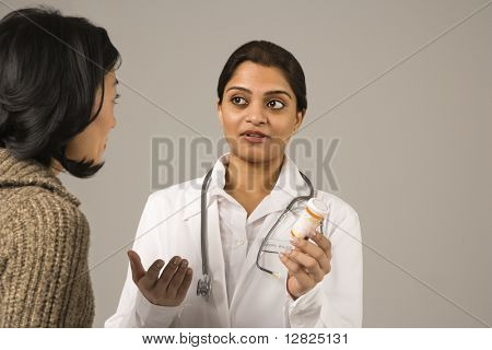 Indian woman doctor explaining medication to Asian woman patient.