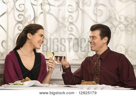 Mid adult Caucasian couple smiling and toasting wine glasses in restaurant.