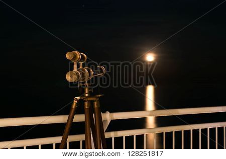 Telescope with amazing moonrising over the sea