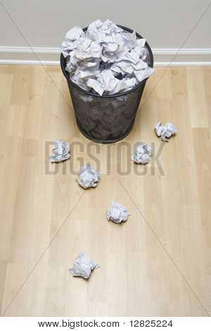 Full wire mesh trash can with crumpled paper scattered around.