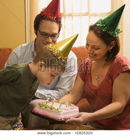 Caucasian boy in party hat blowing out candles on birthday cake with family watching.