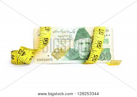 Closeup of five hundred rupee Pakistani currency bill wrapped in measure tape for budget cut concepts